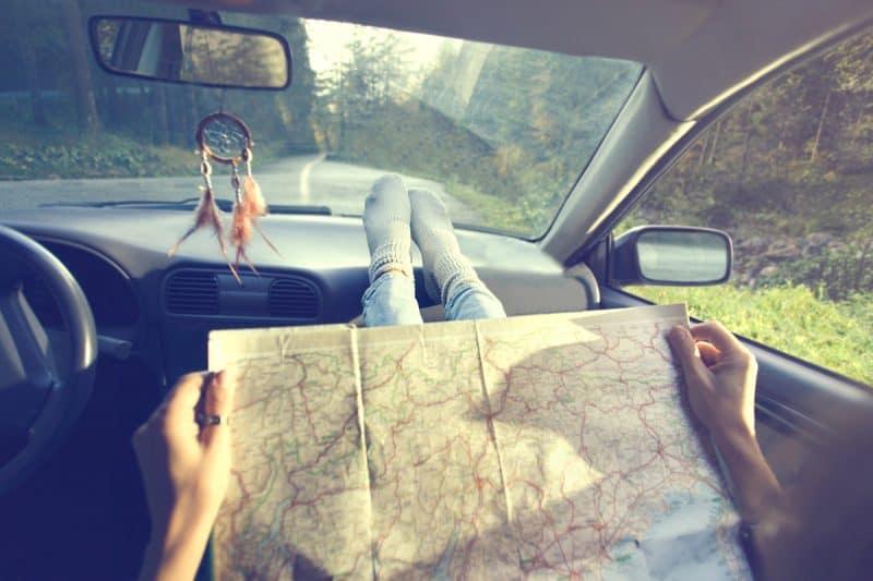En person sitter i bilen med fötterna på instrumentpanelen och läser en gammal karta