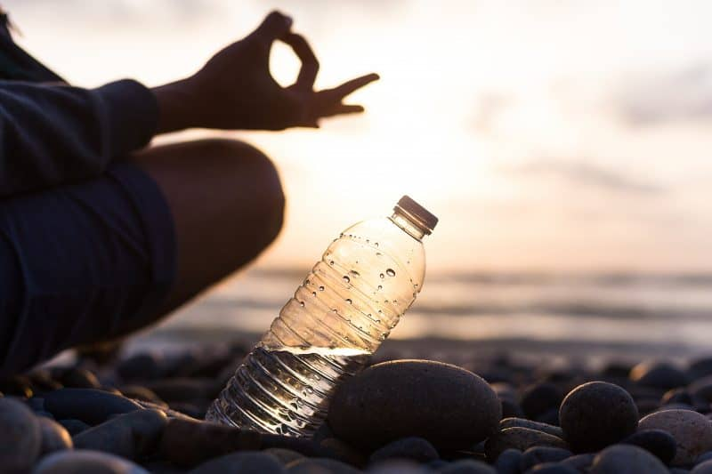 Plastic bottle of water near man, boy doing yoga on the beach at sunset , sunrise time. Yoga finger pose