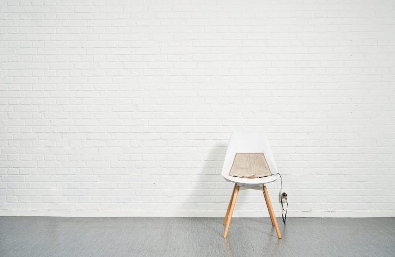 The heated pad Heather in beige on a white chair in front of a white brick wall.