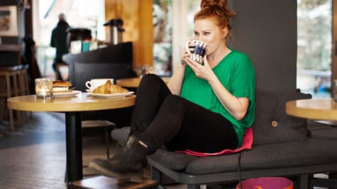 Woman sitting on a Heather at a cafe