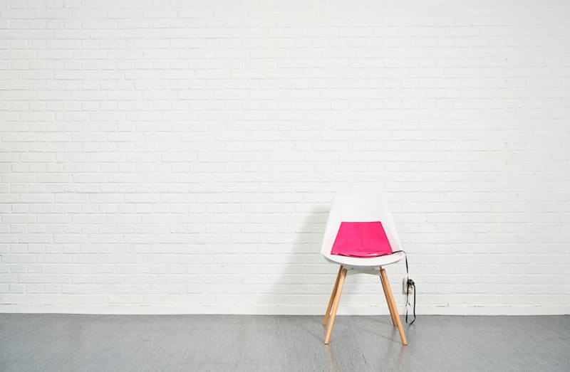 The heated pad Heather in the color pink on a white chair with a white brick background.