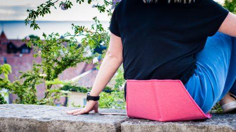 Sittdynan Heather i färgen lollypop pink används av kvinna som sitter på en mur i Visby.