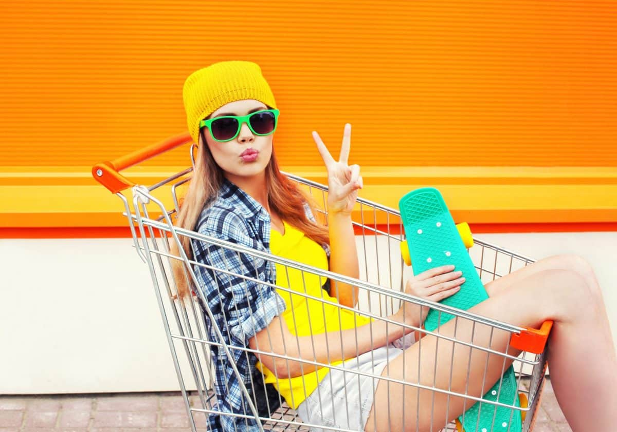 woman in shoppingcart doing victory sign with one hand and holding skate board in the other