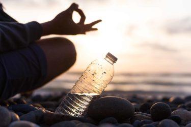 Plastic bottle of water near man, boy doing yoga on the beach at sunset , sunrise time. Yoga finger pose
