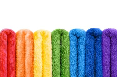 Rainbow colored range of towels on white
