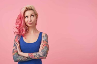 Woman with blond and pink hair and tattoed arms looking up to the right corner thinking of something.